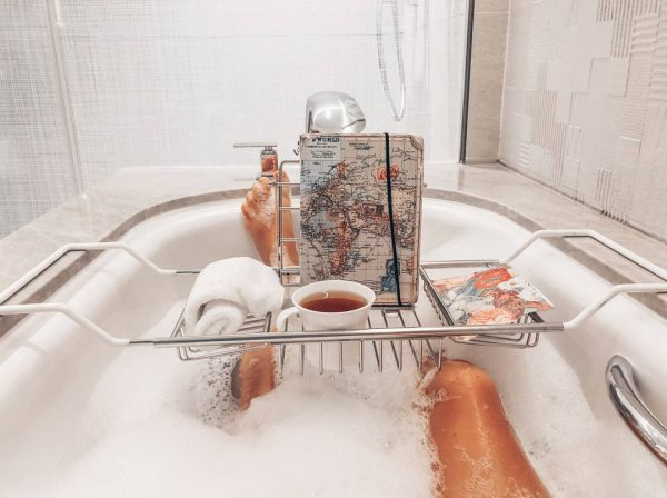 Image of woman's legs in bubble bath from her point of view. There is a basket that hangs across the tub with a cup of tea, journal and map of the world.