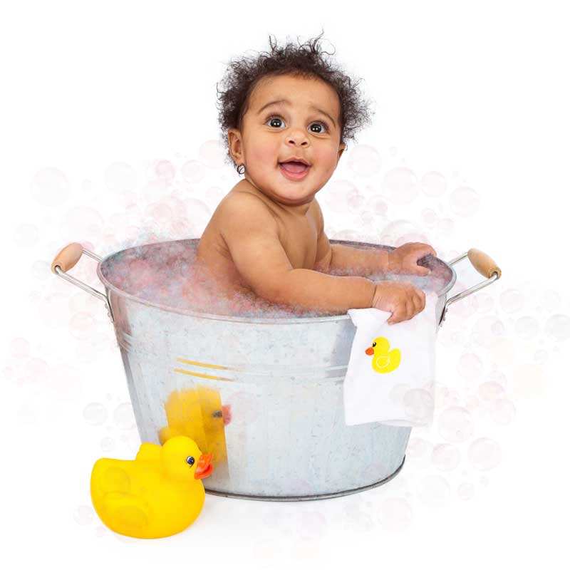 African american toddler in a washbucket bathtub with a rubber duck. He has a cute smile and is holding a rubber duckie washcloth.