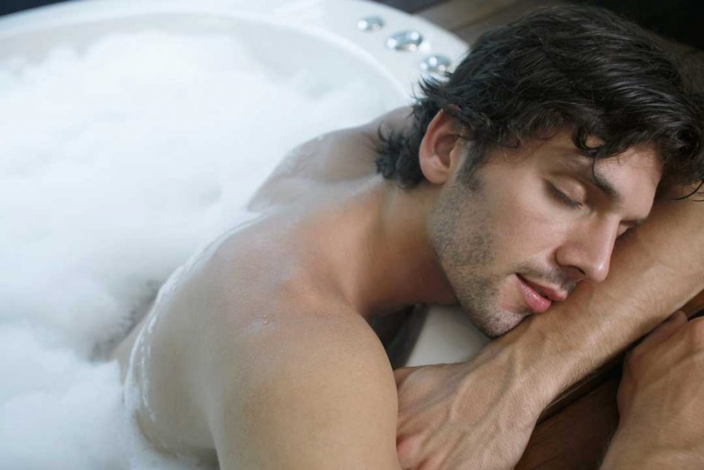 Image of a man falling asleep on the edge of a bathtub. Men were part of a study on hot bath weight loss.