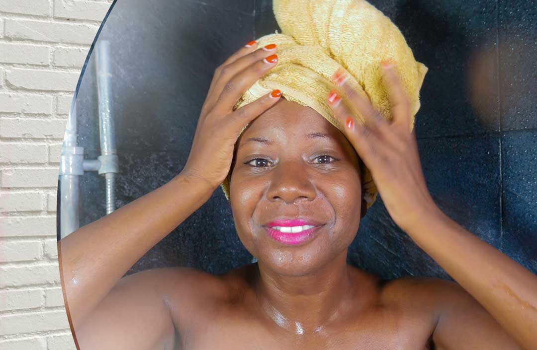 Image of African American woman with towel on her head, just out of the shower. She is looking into the mirror and smiling.