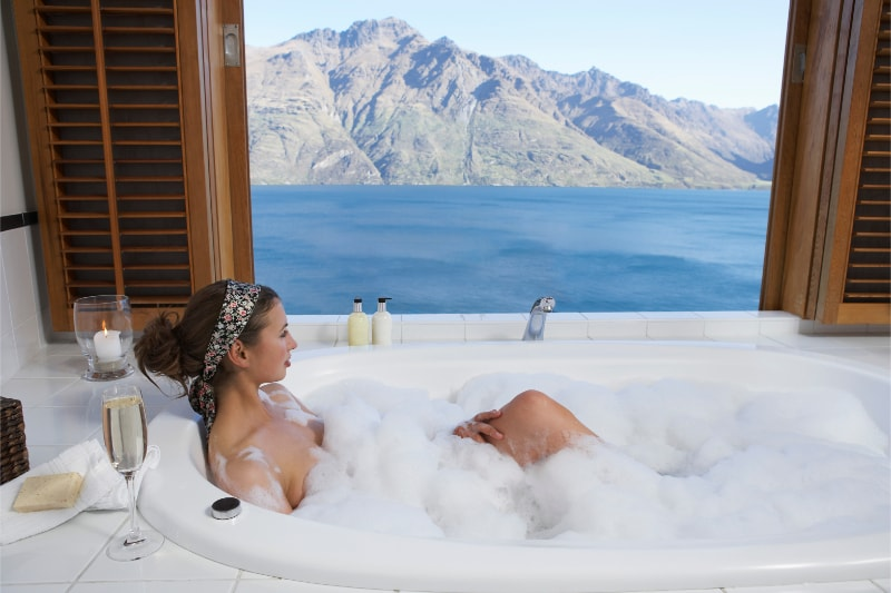 A women soaking a bubble bath to get natural eczema relief. There is a window with a beautiful view of lake and mountains
