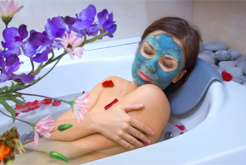 A women soaking in bath to get natural eczema relief. There are flowers in tub and in a vase. She is wearing a beauty mask