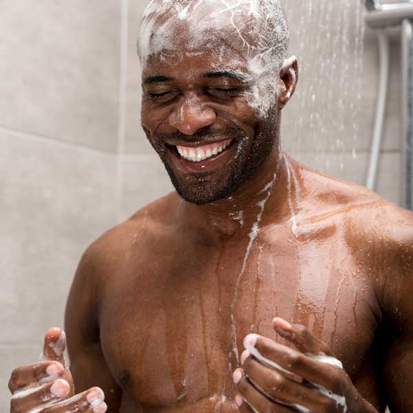 Photo of Black man in shower with shampoo on his hair. He is smiling