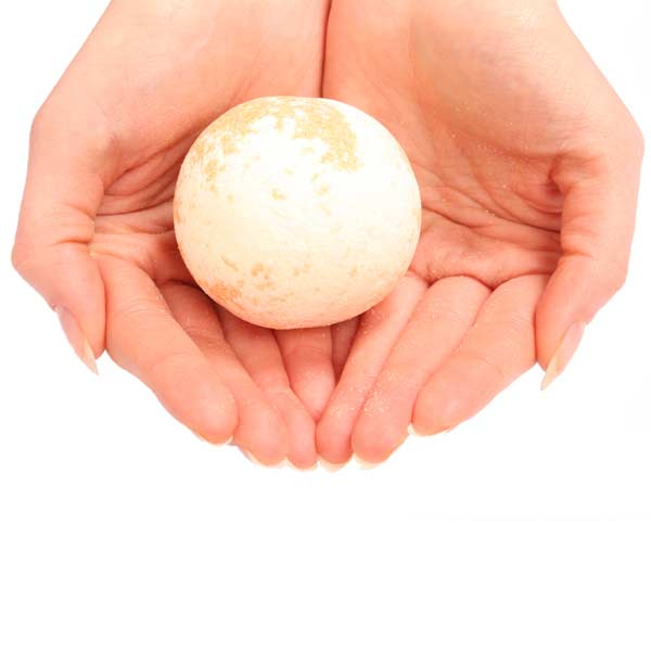 Photo of white woman's hands holding a bathbomb